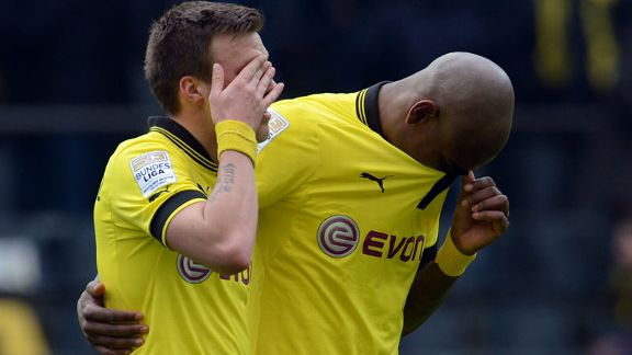 Dortmund's midfielder Kevin Grosskreutz (L) and defender Felipe Santana react to losing their Bundesliga title