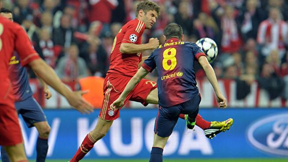 Thomas Muller and Andres Iniesta do battle in the Allianz Arena