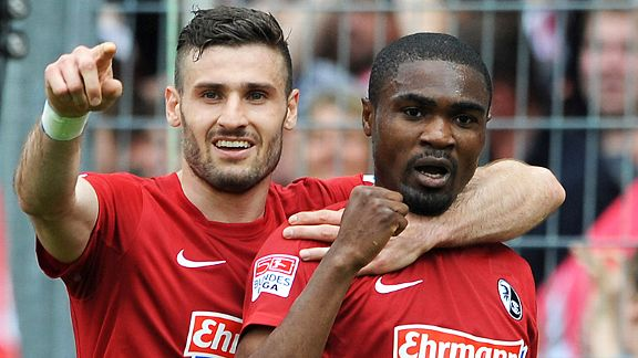 Daniel Caligiuri celebrates with Freiburg goalscorer Cedrick Makiadi