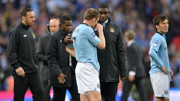James Milner is consoled by Micah Richards after City's defeat