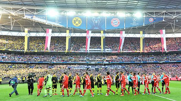 Bayern Munich and Borussia Dortmund players shake hands with their fans split by the half-way line