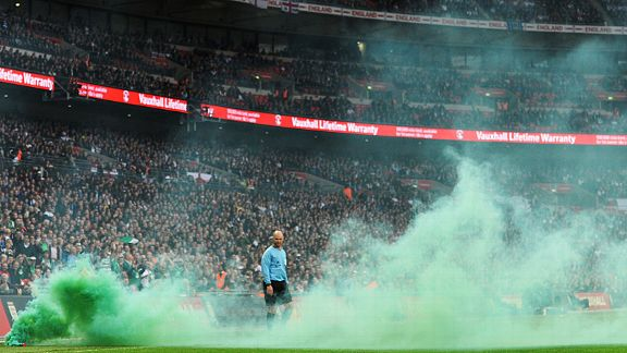 The linesman is englufed after Ireland fans decided to let off a green smoke bomb at Wembley