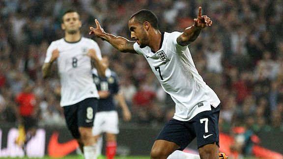 Theo Walcott celebrates his equaliser against Scotland