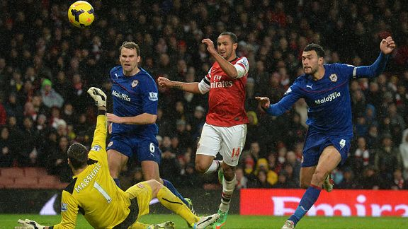Theo Walcott lifts the ball over David Marshall to put Arsenal two up against Cardiff.