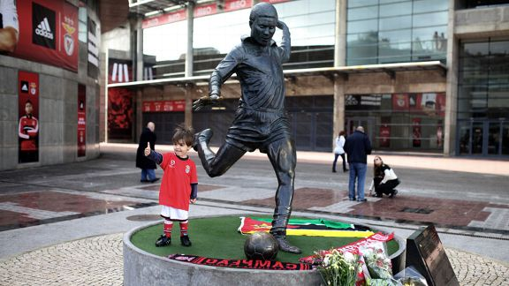A young Benfica fan poses next to the statue of the Portuguese soccer player legend Eusebio at Benfica's Luz stadium in Lisbon