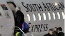 Raymond Domenech boards a plane after defeat to South Africa