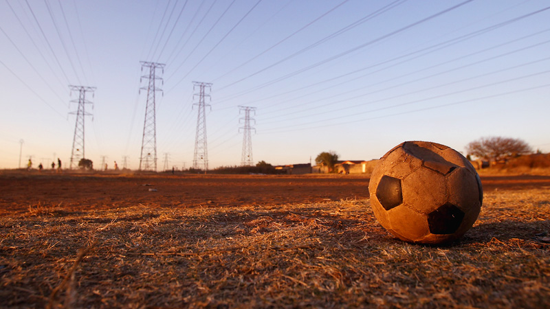 Soccer ball on dirt pitch