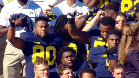 Michigan, Michigan State players raise fists during national anthem