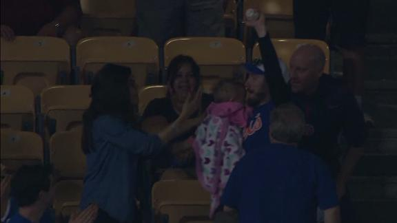 Holding a baby and catching a foul ball is hard