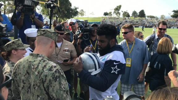 Elliott signs autographs for a marine