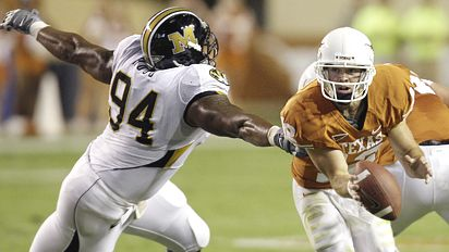 Texas quarterback Colt McCoy, right, is pursued by Missouri defender Ziggy Hood (94) during the first quarter of their NCAA football game in Austin, Texas, Saturday, Oct. 18, 2008. (AP Photo/Eric Gay)