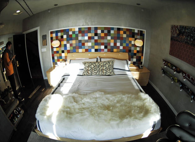 The headboard is made from old pieces of fabric (called swatches) that shoe designers use to determine the materials they want to use on a shoe. They're all recycled from old books of samples.