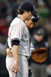 Jorge Posada puts his arm around pitcher Phil Hughes after Hughes' no-hit bid was spoiled by Eric Chavez in the eighth.