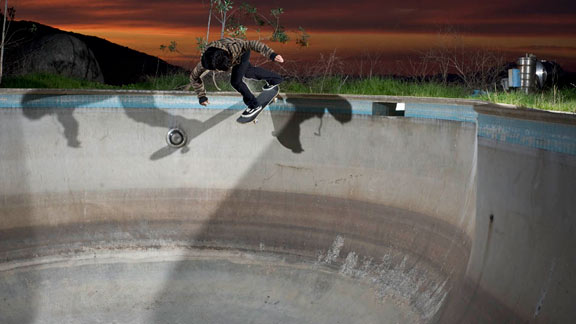 Alex backside tailslides the deep end of a serious pit at sunset
