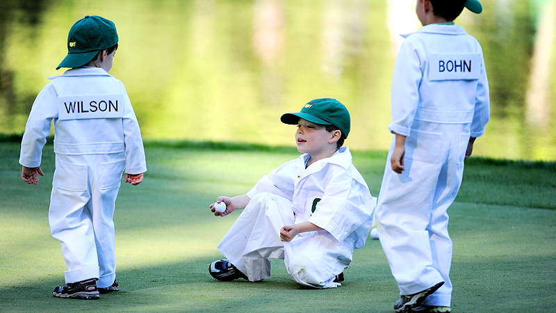 Young caddies wait on a green
