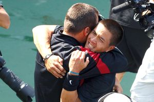 Daniel Nguyen celebrates with coach Peter Smith, left, after USC's third straight men's tennis title.
