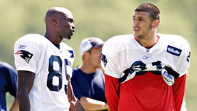 Aaron Hernandez (right) gave Chad Ochocinco No. 85 for free, although Ochocinco said he would have offered the use of his Prius and McDonald's coupons.