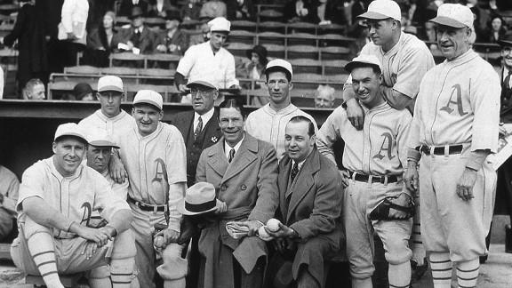 Some of the Philadelphia Athletics pose for a dugout shot before Game 1 of the 1930 World Series. Lefty Grove is standing behind the two men in street clothes, and Jimmie Foxx is leaning on Mule Haas' shoulders.