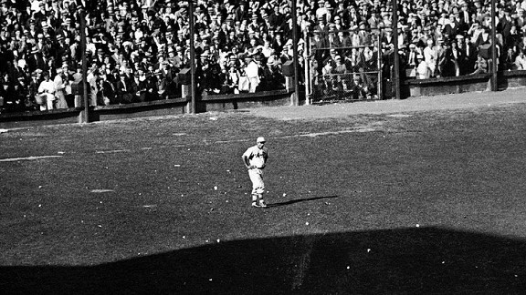 Cardinals left fielder Joe Medwick stands amid debris thrown by irate Tigers fans during Game 7 of the 1934 World Series.