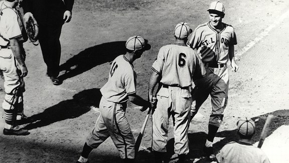The Browns' George McQuinn is congratulated by Gene Moore and Mark Christman after hitting a two-run homer in the 1944 World Series opener.