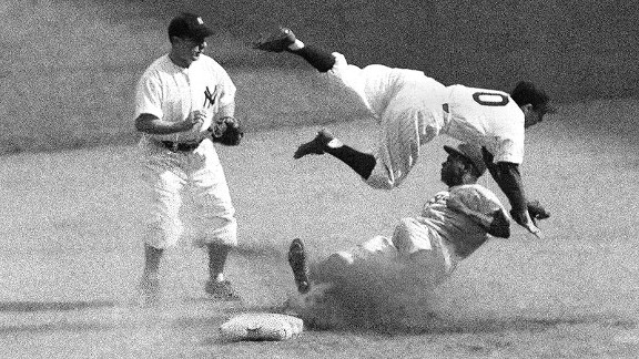 Yankees shortstop Phil Rizzuto sails over the head of the Dodgers' Jackie Robinson at second base during Game 6 of the 1947 World Series.
