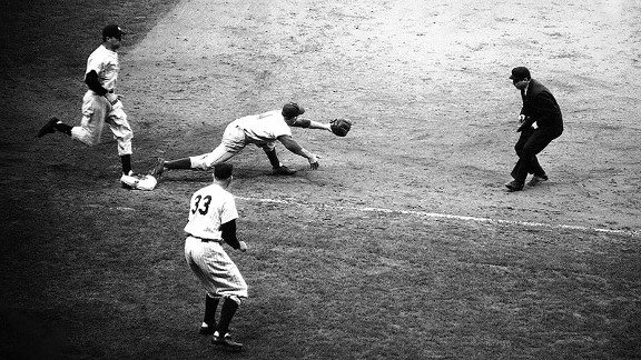 Yankees pitcher Johnny Sain arrives at first base as Dodger first baseman Gil Hodges awaits the throw in the 10th inning of Game 5 of the 1952 World Series. Despite a vehement protest from coach Bill Dickey (33), the umpire called Sain out on the play.