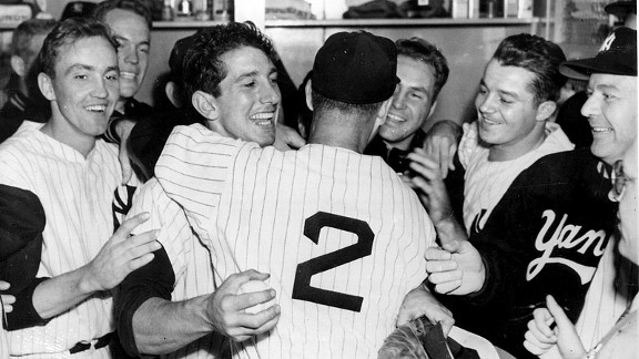 Billy Martin gets a hug from coach Frank Crosetti (2) as his teammates gather around for a victory celebration after Martin's walk-off hit won Game 6 and the 1953 World Series for the Yankees.