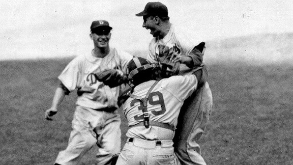 Dodgers pitcher Johnny Podres is lifted by catcher Roy Campanella (39) after the final out of the seventh and deciding game of the 1955 World Series.  Running toward them is third baseman Don Hoak.