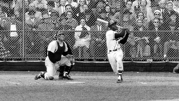 The Braves' Hank Aaron hits a three-run homer during Game 4 of the 1957 World Series.