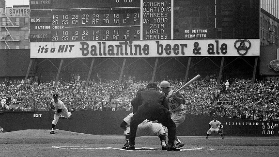 Yankees left-hander Whitey Ford throws the first pitch of the 1961 World Series to the Reds' Don Blasingame. Elston Howard is the catcher, and Ed Runge is the umpire.
