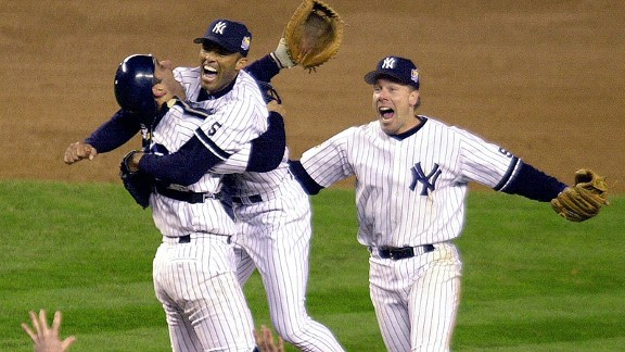 Yankees closer Mariano Rivera gets a hug from catcher Jorge Posada as Scott Brosius joins the celebration after beating the Braves in Game 4 of the 1999 World Series.