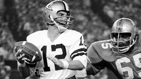 Dallas Cowboys quarterback Roger Staubach (12) found himself in trouble as he rolled to his right and found Houston Oilers' right end Elvin Bethea (65) closing in on him in Houston, Texas on Aug. 31, 1970. Staubach lost ten yards on the first quarter play