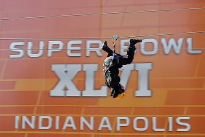 A fan rides a zip line over Super Bowl Village