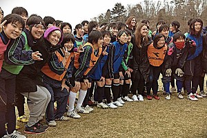 Megan Rapinoe poses with Japanese kids during a soccer clinic in Sendai.