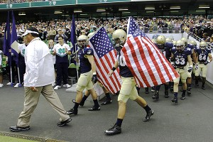 Navy head coach Ken Niumatalolo, left, leads his team onto the field before an NCAA college football game against Notre Dame in Dublin, Ireland,