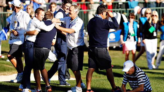 Europe celebrates as Jim Furyk kneels in defeat at the Ryder Cup