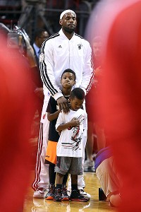 Heat star LeBron James stands with his children during a moment of silence honoring the victims in Newtown, Conn., before a game against the Washington Wizards on Saturday night in Miami.
