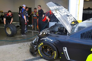 Hendrick Motorsports teammates Jeff Gordon and Kasey Kahne talk with crew members as damage to Gordon's car is evaluated after a 12-car crash during testing at Daytona International Speedway.