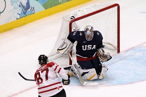 Sidney Crosby #87 of Canada scores the game-winning goal in overtime against Ryan Miller #39 of USA