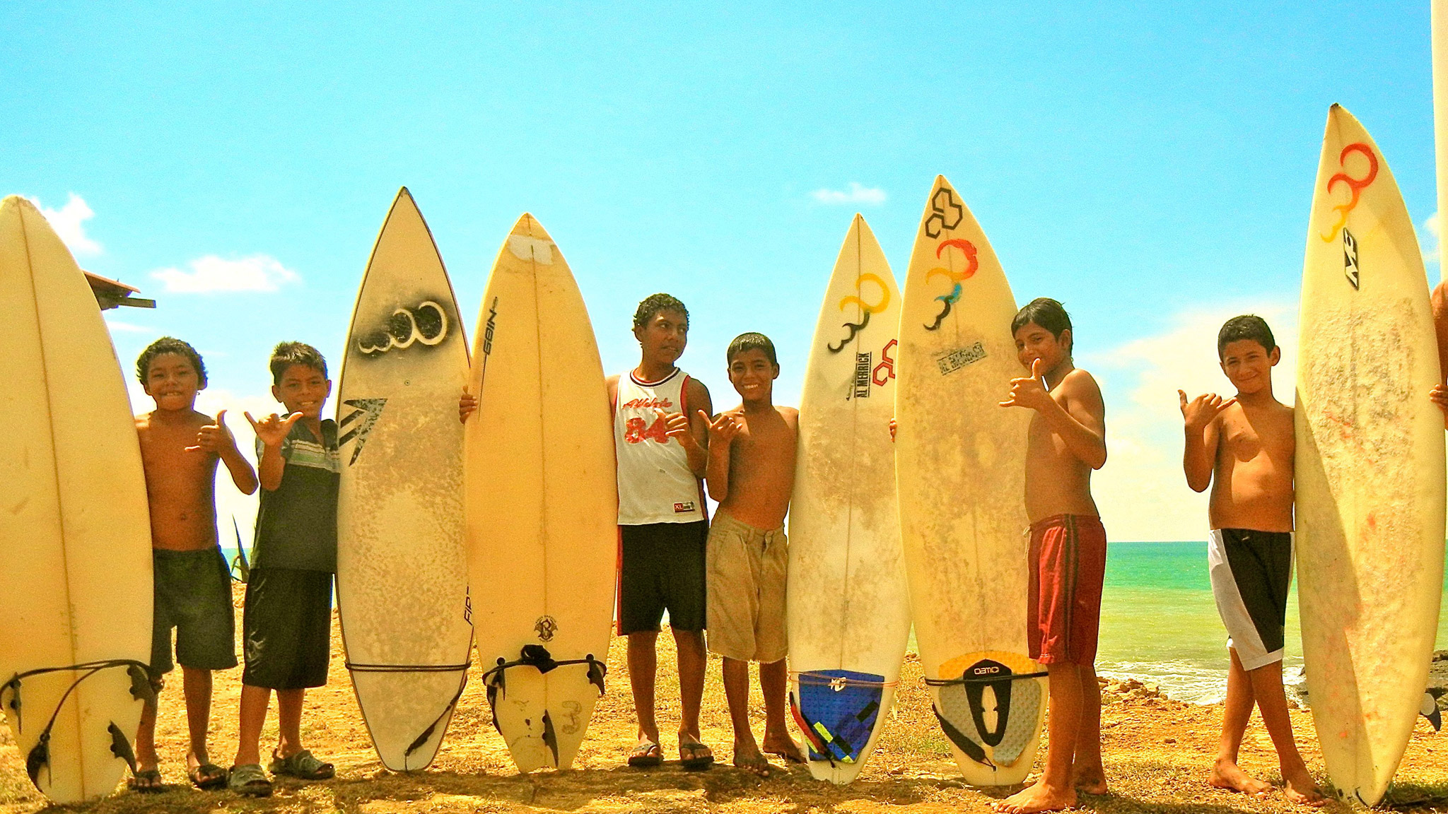 The message is hand ups, not handouts. After a day of cleaning the beaches, the local groms are ready to get wet.