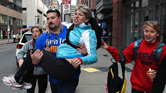 Joe Andruzzi carries a woman from the scene on Exeter Street after two explosions at the Boston Marathon.