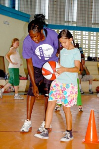 Former Stanford player Shelley Nweke works on a drill with a young girl at a basketball clinic.