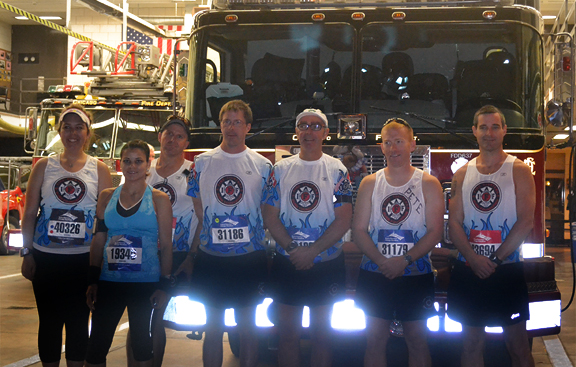 Will Caviness poses with fire fighters before the 2011 Chicago Marathon
