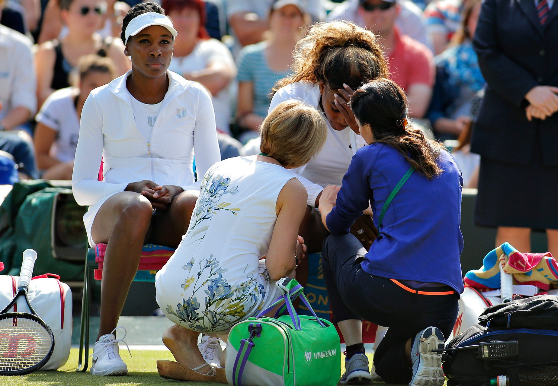 Wimbledon officials talk to Serena Williams as her sister Venus Williams sits in her chair during their women's doubles match against Kristina Barrois of Germany and Stefanie Voegele of Switzerland. Serena was forced to retire with a viral illness.