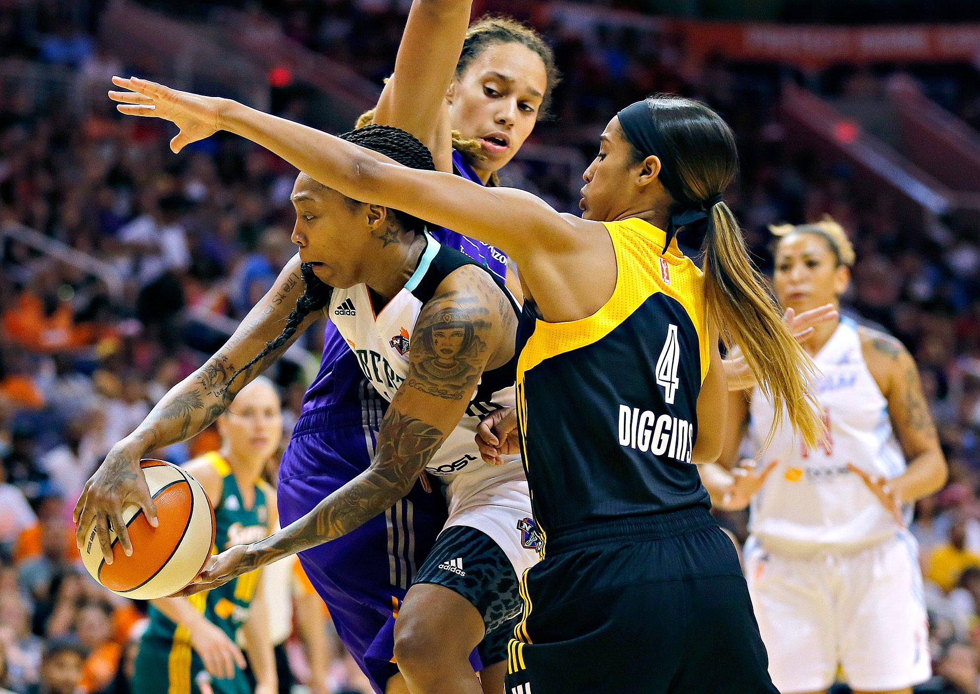 The East's Cappie Pondexter, left, passes between the West's Brittney Griner, rear, and Skylar Diggins during the second half the WNBA All-Star Game. The East won 125-124 in the first WNBA All-Star Game to go to overtime.