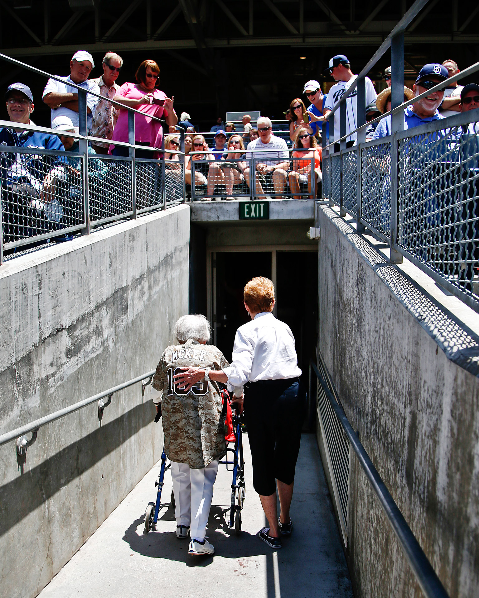 Agnes McKee, a 105-year-old San Diego Padres' fan, leaves the field at Petco Park with fans cheering and taking photos after she threw out the ceremonial first pitch prior to a baseball game.