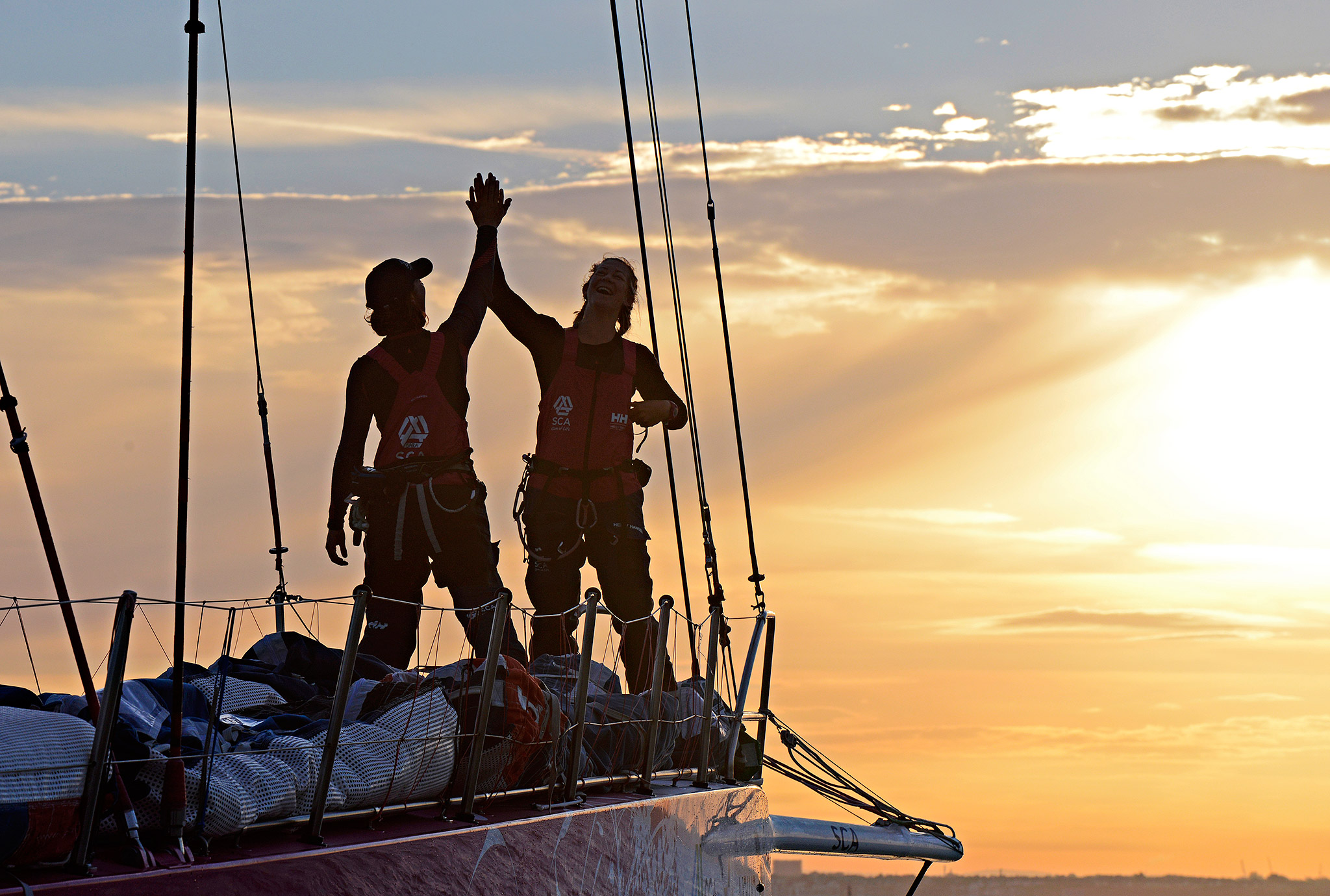 Bowman Sara Hastreiter, United States, and Sophie Ciszek, Australia, high five as Team SCA's Volvo Ocean 65 skippered by Sam Davies finishes at dawn, beating the all-female round Britain record during the Sevenstar Round Britain and Ireland Race.