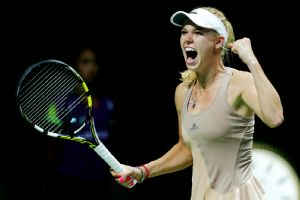 Caroline Wozniacki celebrates after her group-play victory over Maria Sharapova at the WTA Finals.