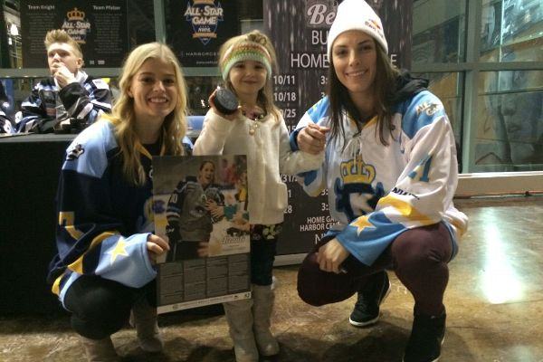 NWHL All-Star Game captains Emily Pfalzer, left, and Hilary Knight visit with a young fan during festivities.