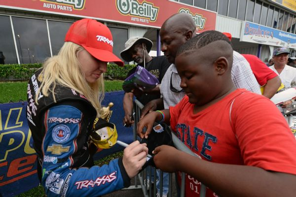 Courtney Force signs merchandise for fans after her NHRA Funny Car SpringNationals win in Houston on May 1.